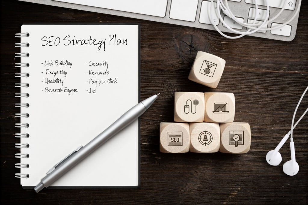 seo strategy written in notebook next to keyboard and blocks