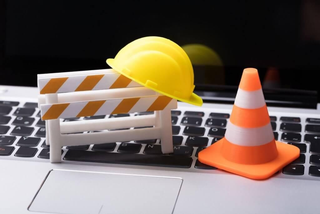 Website maintenance concept, construction toys on laptop